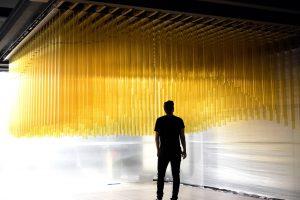"""Die Design-Agentur """"Scandinavian Design Group"""" simuliert die Bewegungen des Ozeans in ihrer interaktiven Installation """"Breaking the Surface"""". Motorenbetriebene Plexiglasstangen bewegen sich auf und ab. Besucher können sich frei durch die Installation bewegen, ohne dass sie von den Stangen berührt werden.[15]."""